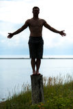 Mensensilhouet die Yoga op een Stomp in Aard doen Royalty-vrije Stock Foto's