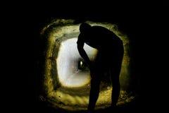 Mensensilhouet in een hol of een droog kanaal van het zandsteenwater, achterschot Het bezoeken van oude ondergronds stock foto