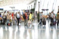 Mensensilhouetten in motieonduidelijk beeld, luchthavenbinnenland Stock Foto