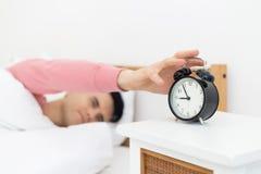 Mensenslaap in bed vroeg kielzog die omhoog genoeg slaap niet worden stock afbeelding