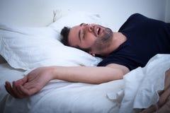 Mensenslaap in zijn bed en het snurken stock foto