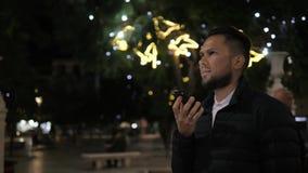 Mensenspraakherkenning met smartphone in het hotelbar van de parknacht openlucht, vinder van de het bericht audiohelper van het s stock footage