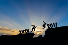 Mensensprong tussen 2016 en 2017 jaar op zonsondergangachtergrond Stock Afbeeldingen