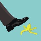 Mensenstap op banaanschil, bedrijfsconcept Royalty-vrije Stock Fotografie