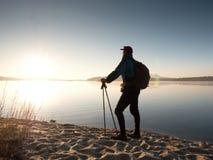 Mensentoerist met een rugzak en trekkingspolen die zich op zandig strand bevinden De wandelaar geniet van stock afbeelding