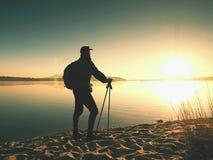 Mensentoerist met een rugzak en trekkingspolen die zich op zandig strand bevinden De wandelaar geniet van royalty-vrije stock afbeeldingen
