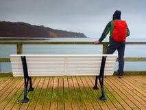 Mensentoerist met rode rugzak op houten overzeese pijler De regenachtige dag van de herfst Stock Fotografie