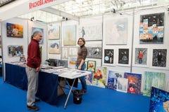 Mensentribunes bij de cabine met schilderijen en besprekingen aan de kunstenaar royalty-vrije stock foto