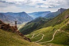 Mensentribunes op de rand van een klip Een mening van de pas en de prachtige vallei royalty-vrije stock fotografie