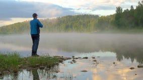 Mensentribunes op steen tegen het uitspreiden van mist over kalm water stock footage