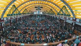 Mensenviering van Oktoberfest in grote biertent Beieren, Duitsland stock video