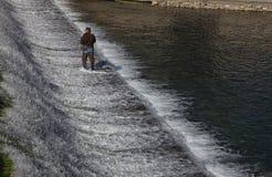Mensenvlieg die op een rivierdam vissen Stock Foto