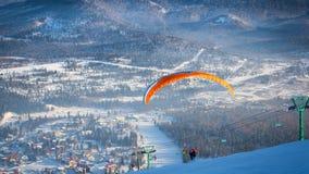 Mensenvliegen met een oranje valscherm Stock Afbeeldingen