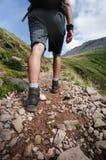 Mensenwandelaar die op bergrotsen lopen met stokken Mooi weer met de aard van Schotland Detail van wandelingslaarzen op moeilijk  Stock Fotografie