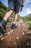 Mensenwandelaar die op bergrotsen lopen met stokken Mooi weer met de aard van Schotland Detail van wandelingslaarzen op moeilijk  Royalty-vrije Stock Fotografie