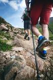 Mensenwandelaar die op bergrotsen lopen met stokken Mooi weer met de aard van Schotland Detail van wandelingslaarzen op moeilijk  Royalty-vrije Stock Foto's