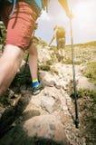 Mensenwandelaar die op bergrotsen lopen met stokken Mooi weer met de aard van Schotland Detail van wandelingslaarzen op moeilijk  Stock Afbeeldingen