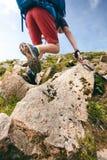 Mensenwandelaar die op bergrotsen lopen met stokken Mooi weer met de aard van Schotland Detail van wandelingslaarzen op moeilijk  Royalty-vrije Stock Afbeelding