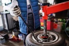 Mensenwerktuigkundige die een auto in een garage herstellen stock fotografie