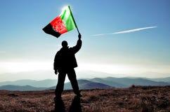 Mensenwinnaar die Afganistan-vlag golven Stock Fotografie