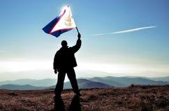 Mensenwinnaar die Amerikaanse Samoaman-vlag golven Stock Afbeeldingen