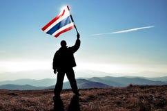 Mensenwinnaar die de vlag van Thailand bovenop de bergpiek golven Royalty-vrije Stock Fotografie