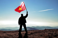 Mensenwinnaar die de vlag van Vietnam bovenop de bergpiek golven Stock Fotografie