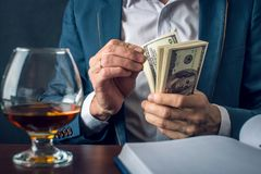 Mensenzakenman in het geld van de kostuumholding in zijn handen Steekpenning in de vorm van dollarrekeningen Concept corruptie en stock fotografie