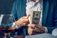 Mensenzakenman in het geld van de kostuumholding in zijn handen Steekpenning in de vorm van dollarrekeningen Concept corruptie en royalty-vrije stock foto
