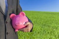 Mensenzakenman Holding Piggy Bank op Gebied royalty-vrije stock fotografie