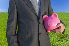 Mensenzakenman Holding Piggy Bank op Gebied royalty-vrije stock foto's
