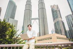 Mensenzakenman of student in toevallige kleding die laptop in een tropisch park op de achtergrond van wolkenkrabbers met behulp v Royalty-vrije Stock Fotografie