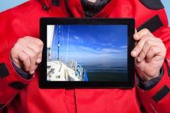 Mensenzeeman die jachtboot op tablet tonen sailing stock afbeelding