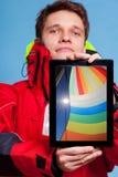 Mensenzeeman die zeilboot op tablet tonen sailing royalty-vrije stock foto's