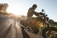 Mensenzetel op de motorfiets op de bosweg Royalty-vrije Stock Fotografie