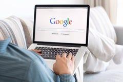 Mensenzitting bij de MacBook-retina met plaats Google op het scherm Stock Afbeelding