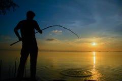 Mensenzitting bij de visserij bij zonsondergang Royalty-vrije Stock Afbeelding