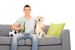 Mensenzitting bij laag met zijn puppy en voetbal Stock Fotografie
