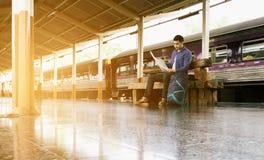 Mensenzitting bij station en het kijken op kaart voor reis plann Stock Fotografie