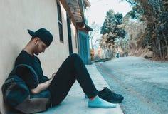 Mensenzitting die met zijn mobiel rusten stock fotografie
