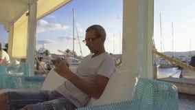 Mensenzitting in een koffie in de jachthaven en het gebruiken van zijn telefoon stock footage