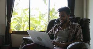 Mensenzitting in Leunstoel die Laptop Computer Typen gebruiken die, Guy Surfing Internet Happy Smiling thuis werken stock videobeelden