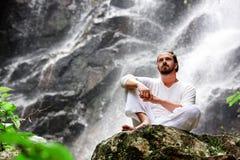 Mensenzitting in meditatieyoga op rots bij waterval in tropisch royalty-vrije stock fotografie