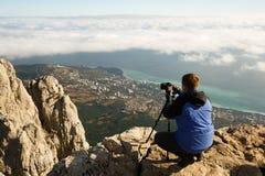 Mensenzitting met een driepoot en fotocamera op een hoge bergpiek boven wolken, stad en overzees Profotograaf Stock Foto's