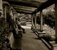 Mensenzitting op bank in tuinen Royalty-vrije Stock Afbeelding