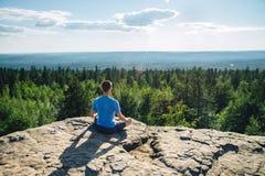 Mensenzitting op de bovenkant van de berg in meditatiezitting in Lotus Posture, padmasana, het praktizeren pranayama Stock Foto's