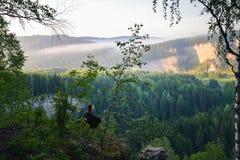 Mensenzitting op de bovenkant van de berg, vrije tijd in harmpny met aard Royalty-vrije Stock Fotografie