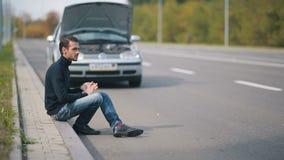 Mensenzitting op de weg in een voorzijde van gebroken auto stock videobeelden