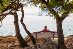 Mensenzitting op een bank op de kust Royalty-vrije Stock Afbeeldingen