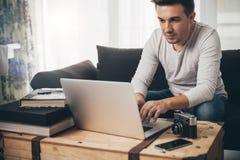Mensenzitting op een bank die aan laptop werken Royalty-vrije Stock Afbeelding